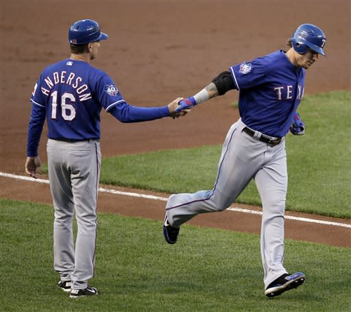 Texas Rangers' Josh Hamilton, right, shakes hands with third base coach Dave Anderson as he rounds the bases after hitting a two-run home run in the first inning of the second baseball game of a doubleheader in Baltimore, Thursday, May 10, 2012. (AP Photo/Patrick Semansky)