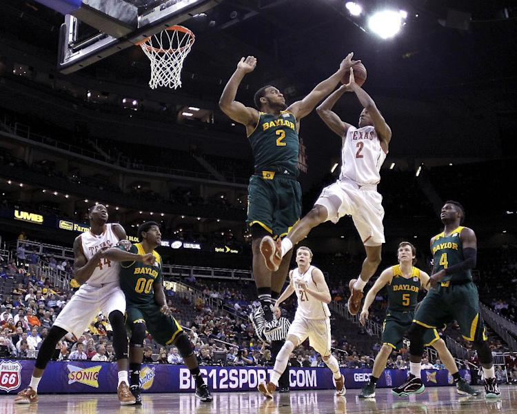 Baylor's Rico Gathers, left, blocks a shot by Texas' Demarcus Holland during the second half of an NCAA college basketball game in the Big 12 men's tournament Friday, March 14, 2014, in Kansas City, Mo. Baylor won 86-69. (AP Photo/Charlie Riedel)