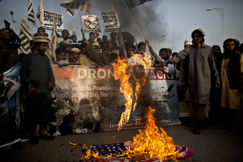 Supporter of the Pakistani religious party Jamaat-u-Dawa, burn a representation of a U.S flag, during a rally to condemn U.S. drone attacks in Pakistan, in Islamabad, Pakistan, Friday, Nov. 1, 2013. (AP Photo/Muhammed Muheisen)