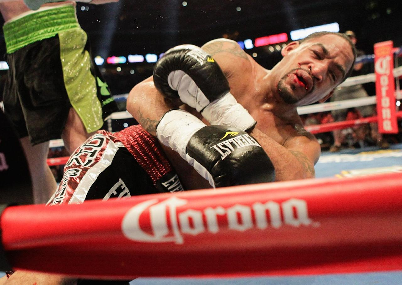 "James Kirkland lies on the mat after being knocked out by Saul ""Canelo"" Alvarez during the third round during of a 154-pound boxing bout Saturday, May 9, 2015, in Houston. (AP Photo/Bob Levey)"