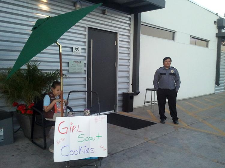 Lexi Menees, 8, sells Girl Scout Cookies while sitting outside Trumed Dispensary, which sells medical marijuana for licensed patients, in Phoenix on Friday, Feb. 21, 2014. Girl Scouts seem to be foregoing the usual supermarket stops for selling their beloved cookies. A few days after a teenager sold dozens of cookie boxes outside a San Francisco pot dispensary, Menees, 8, will return to Trumed Dispensary in Phoenix on Saturday for the same purpose. The girl's mother, Heidi Carney, got the idea after hearing about what happened in San Francisco. Susan de Queljoe, a spokeswoman for the Girl Scouts, Arizona Cactus-Pine Council, says this is not something the organization would encourage but that it's up to the parents. (AP Photo/Terry Tang)