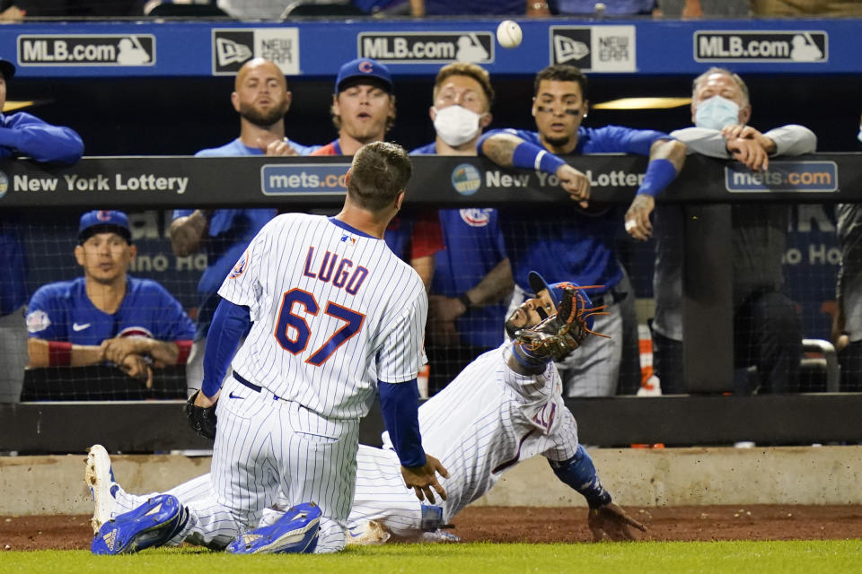 Chicago Cubs watch as New York Mets' Jonathan Villar, right, and relief pitcher Seth Lugo attempt to catch a foul ball by Anthony Rizzo during the ninth inning of a baseball game Tuesday, June 15, 2021, in New York. (AP Photo/Frank Franklin II)