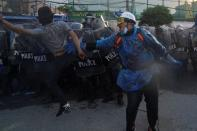 Demonstrators clash with riot police officers during an anti-government protest in Bangkok