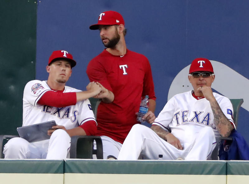 Texas Rangers' Kyle Bird, left, shakes hands with Chris Martin, center, as Jesse Chavez watches play in the third inning of a baseball game against the Seattle Mariners in Arlington, Texas, Tuesday, July 30, 2019. Martin was traded to the Atlanta Braves for a pitching prospect. (AP Photo/Tony Gutierrez)