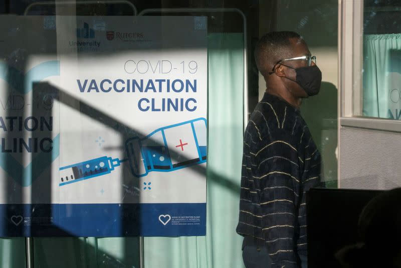 A man walks by the area where people get vaccine at University Hospital's COVID-19 vaccine clinic at Rutgers New Jersey Medical School in Newark, New Jersey