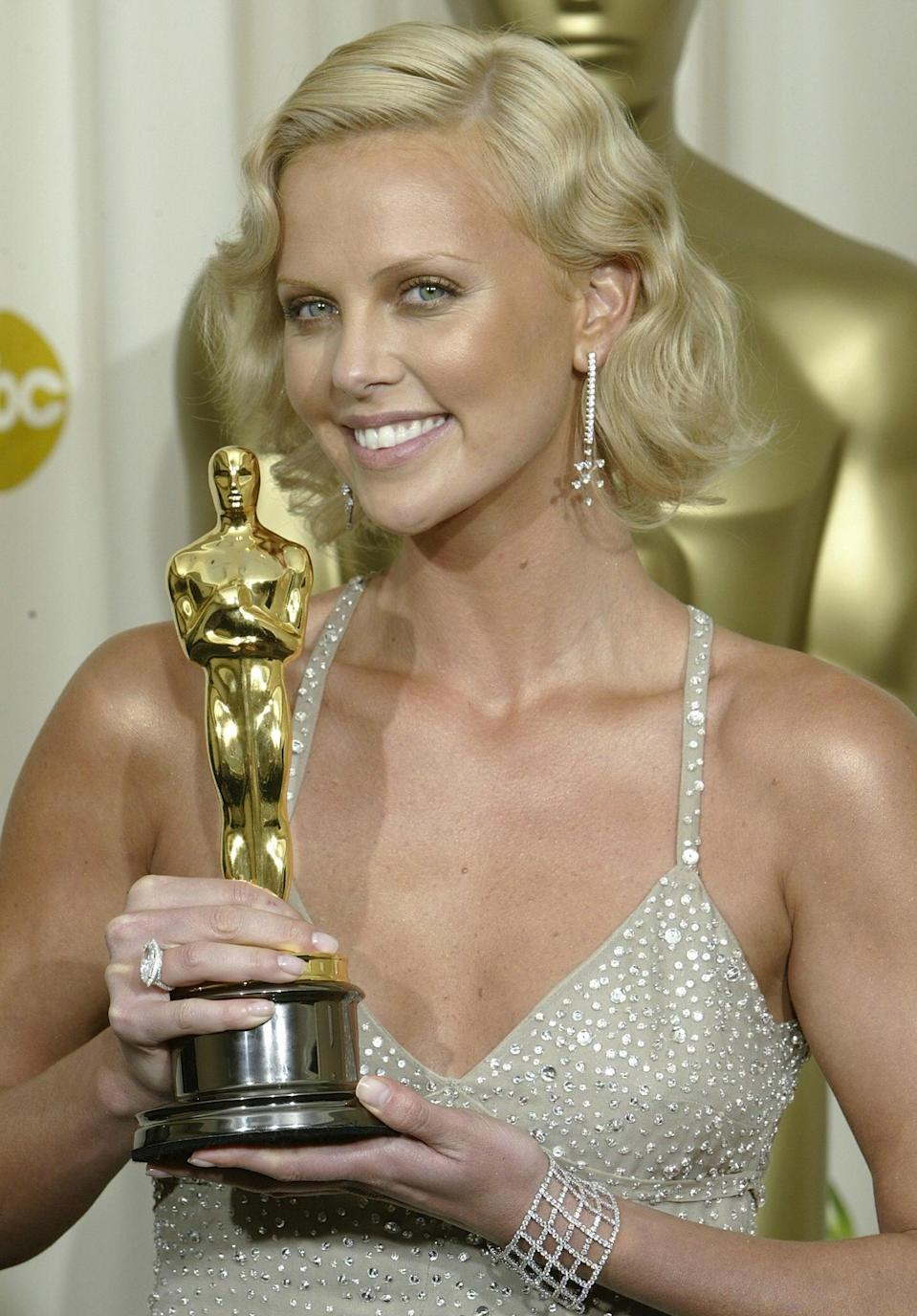 """<p><a class=""""link rapid-noclick-resp"""" href=""""https://www.popsugar.com/Charlize-Theron"""" rel=""""nofollow noopener"""" target=""""_blank"""" data-ylk=""""slk:Charlize Theron"""">Charlize Theron</a> styled her bob haircut into fingerwaves at the Oscars in 2004. </p>"""