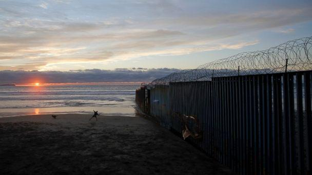 PHOTO: In this Jan. 9, 2019, file photo, a man throws a ball for his dog next to the border wall topped with razor wire in Tijuana, Mexico. (AP)