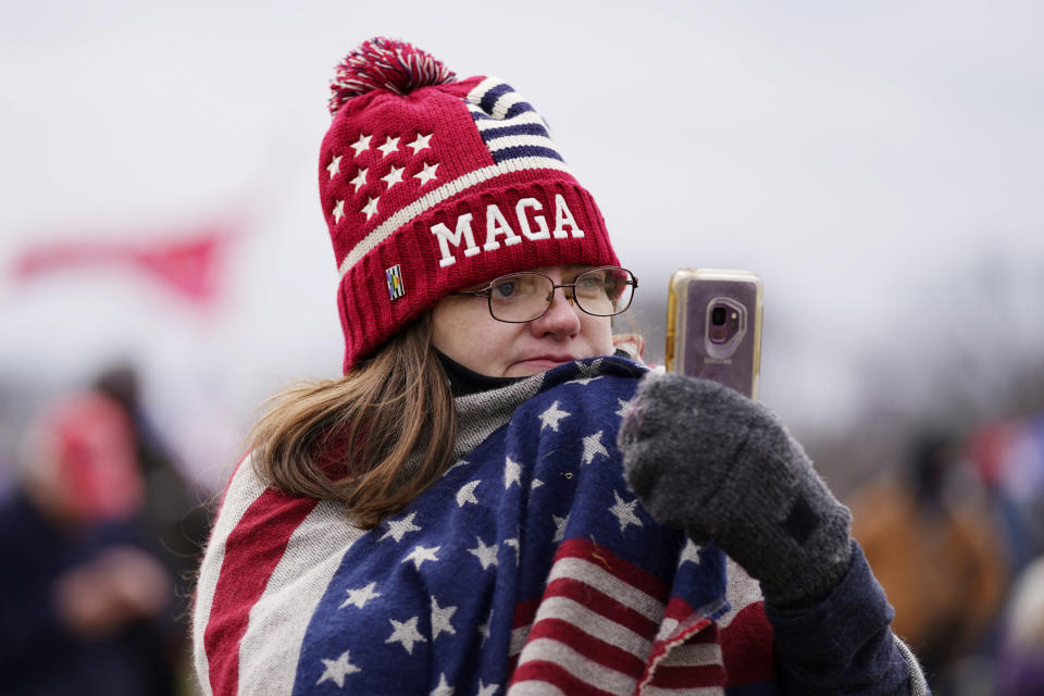 FILE - In this Jan. 6, 2021, file photo, a Trump supporter participates in a rally in Washington. Online supporters of Trump are scattering to smaller social media platforms, fleeing what they say is unfair treatment by Facebook, Twitter and other big tech firms looking to squelch misinformation and threats of violence. (AP Photo/Julio Cortez, File)