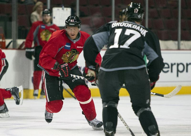 Chicago Blackhawks right wing Marian Hossa, left, keeps his eye on the puck while defenseman Sheldon Brookbank prepares to block him during NHL hockey practice Friday, June 14, 2013, in Chicago. The Blackhawks lead the Boston Bruins 1-0 in the best-of-seven games Stanley Cup final series. Game 2 is scheduled for Saturday in Chicago. (AP Photo/Scott Eisen)