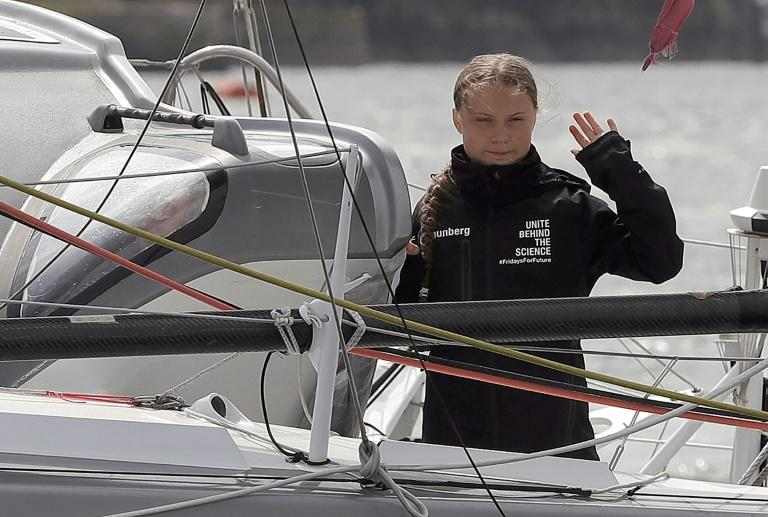 Swedish climate activist Greta Thunberg waves from aboard the Malizia II IMOCA class sailing yacht which is taking her to New York
