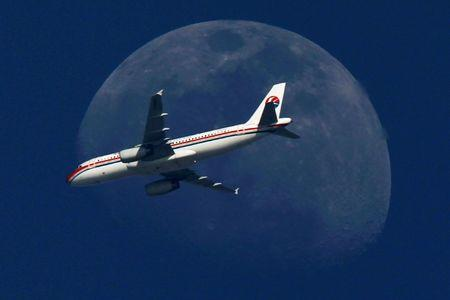 FILE PHOTO - A China Eastern Airlines passenger jet passes in front of the moon over Shanghai