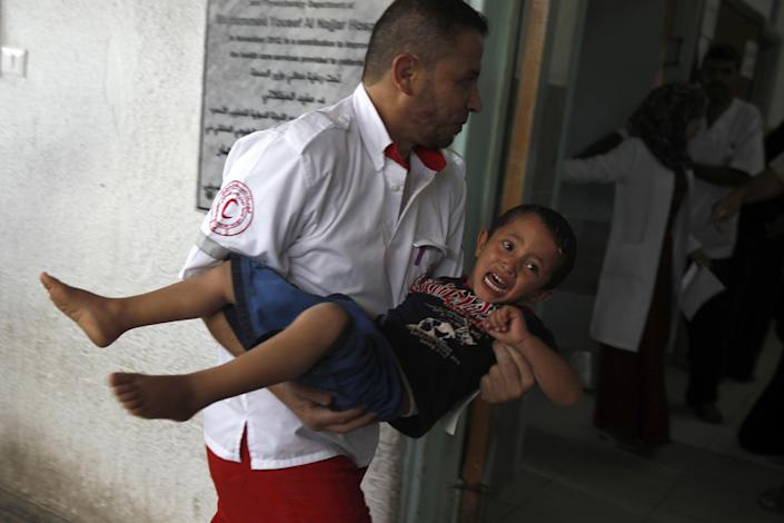 A member of the Palestinian Red Crescent Society carries an injured child at a hospital in Rafah, in southern Gaza, following an Israeli air strike on July 17, 2014 (AFP Photo/Said Khatib)