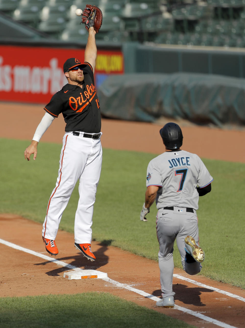 Baltimore Orioles first baseman Chris Davis, left, is unable to catch a high throw from starting pitcher Alex Cobb, not visible, on a dribbler hit by Miami Marlins' Matt Joyce (7) during the second inning in game one of a baseball double-header, Wednesday, Aug. 5, 2020, in Baltimore. (AP Photo/Julio Cortez)