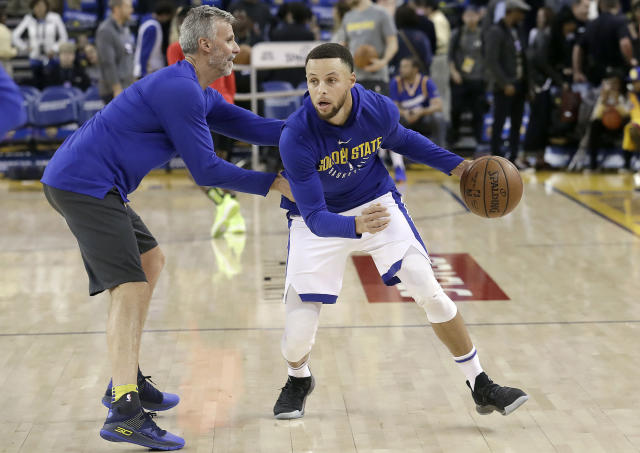 Stephen Curry (right) warms up with assistant coach Bruce Fraser before the Warriors' game against the Hawks. (AP)