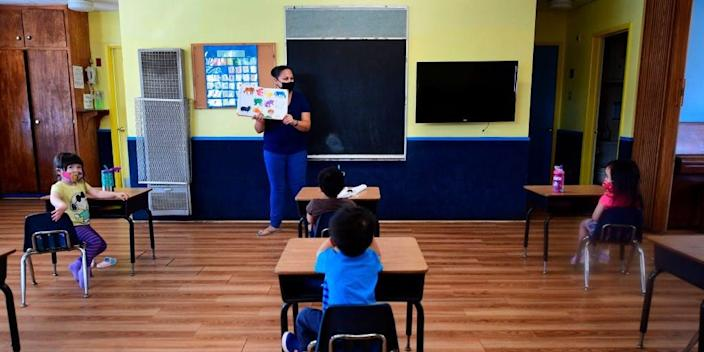 Instructor Chablis Torres (C) reads to children in a pre-school class, wearing masks and at desks spaced apart as per coronavirus guidelines during summer school sessions at Happy Day School in Monterey Park, California on July 9, 2020.