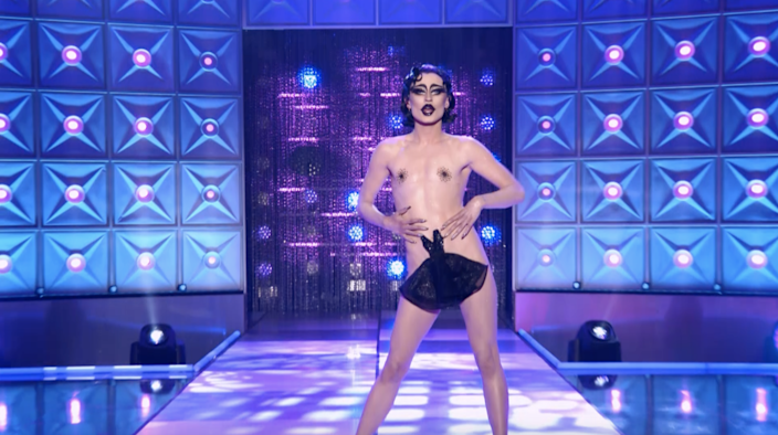"""A drag queen wearing a """"little black dress""""-shaped piece of fabric over her crotch."""