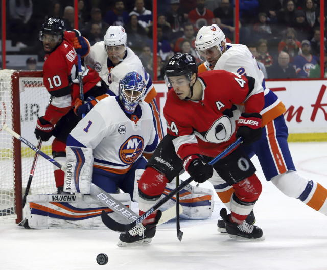 Ottawa Senators center Jean-Gabriel Pageau (44) tries to control the puck in front of New York Islanders goaltender Thomas Greiss (1) as Islanders defenseman Nick Leddy (2) defends during first-period NHL hockey game action in Ottawa, Ontario, Thursday, March 7, 2019. (Fred Chartrand/The Canadian Press via AP)