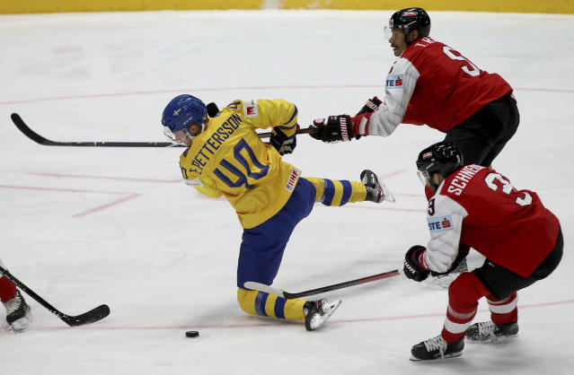 Sweden's Elias Pettersson, left, checks Austria's Thomas Raffl and Peter Schneider, right, during the Ice Hockey World Championships group B match between Sweden and Austria at the Ondrej Nepela Arena in Bratislava, Slovakia, Thursday, May 16, 2019. (AP Photo/Ronald Zak)