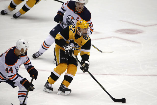 Pittsburgh Penguins' Sidney Crosby (87) works the puck between Edmonton Oilers' Connor McDavid (97) and Zack Kassian (44) during the first period of an NHL hockey game in Pittsburgh, Saturday, Nov. 2, 2019. (AP Photo/Gene J. Puskar)