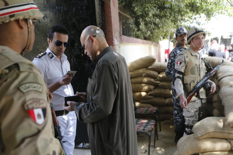 A policeman checks a voter identity card as he enters a polling station in Cairo, Egypt, Saturday, April 20, 2019. Egyptians are voting on constitutional amendments that would allow el-Sissi to stay in power until 2030. (AP Photo/Amr Nabil)