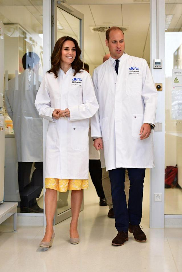 The royal couple covered up in lab coats while at a cancer research facility. (Photo: PA)