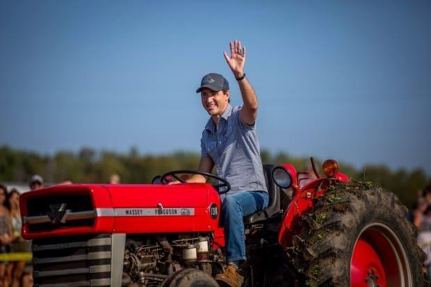 Justin Trudeau drives a tractor at the International Plowing Match and Rural Expo in Walton, Ont., on Friday, September 22, 2017. Research suggests a rural-urban split between Liberal and Conservative supporters has been deepening since the 1960s. (Chris Donovan/Canadian Press - image credit)