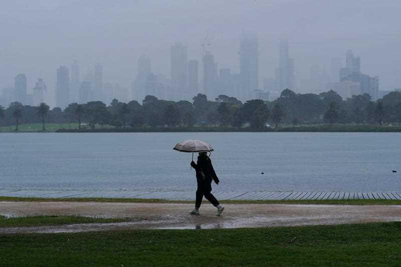 People walk in isolation as heavy rain begins to fall in Melbourne.