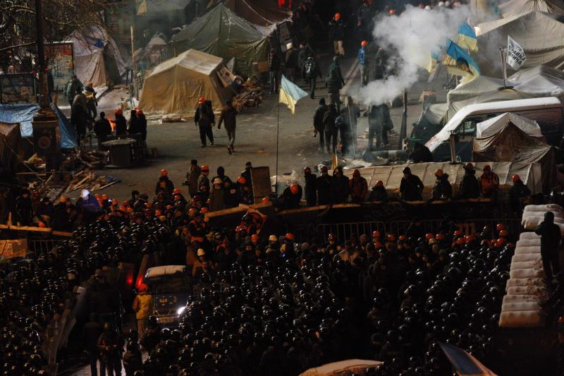 """Riot police block Pro-European Union activists camping out in their tents on the Independence Square in Kiev, Ukraine, Wednesday, Dec. 11, 2013. Hundreds of police have moved on a large protest camp in the center of Kiev. Protesters are shouting """"Shame!"""" """"We will stand!"""" and singing the Ukrainian national anthem. (AP Photo/Alexander Zemlianichenko)"""
