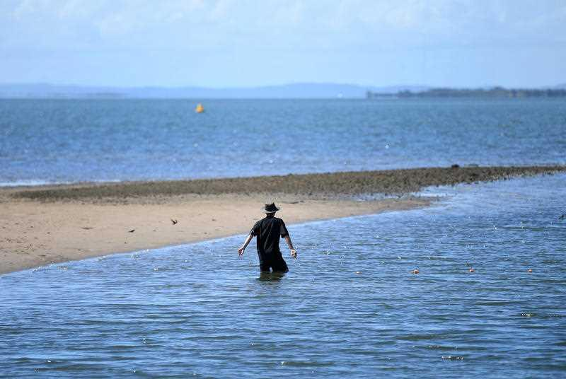 A man is seen fishing in shallow water off the Wynnum foreshore in Brisbane