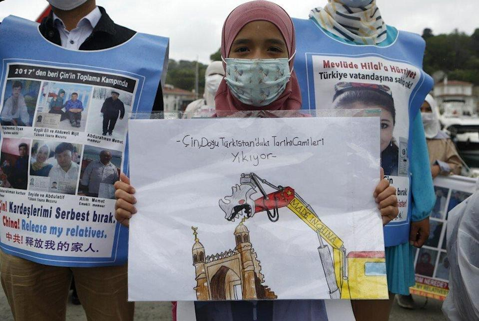 """A woman holds a placard that reads """"China is destroying historical mosques in East Turkistan"""", using an unofficial name for Xinjiang, as members of the Uyghur community living in Turkey stage a protest outside the Chinese consulate in Istanbul on Wednesday. Photo: AP"""