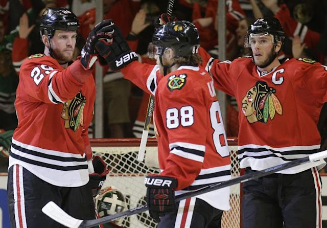 Chicago Blackhawks' Bryan Bickell (29), left, celebrates with Patrick Kane (88) and Jonathan Toews (19) after scoring his goal against the Minnesota Wild during the second period in Game 5 of an NHL hockey second-round playoff series in Chicago,Sunday, May 11, 2014. (AP Photo/Nam Y. Huh)