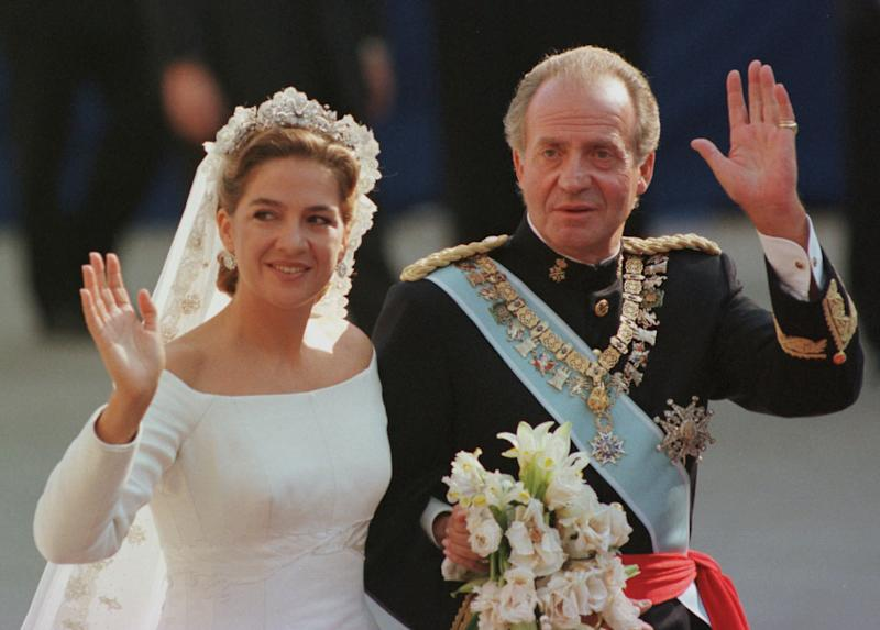 In this Oct. 4, 1997 file photo, Spain's Princess Cristina, left is escorted to the Barcelona cathedral by her father King Juan Carlos prior to getting married to Inaki Urdangarin. In an unprecedented court appearance on Saturday Feb. 8, 2014 for a direct descendent of a Spanish king, Princess Cristina will answer questions from a judge who has formally named her as a fraud and money laundering suspect. The case is a direct offshoot of one led by the same judge in an investigation of her husband Inaki Urdangarin for allegedly using his position as the Duke of Palma to embezzle public contracts via the Noos Institute, a supposedly nonprofit foundation he set up that channeled money to other businesses. Spain's royal family just wants the case that has now dragged on for years to end rapidly so the monarchy can try to rebuild the trust it once had. (AP Photo/Armando Franca, File)