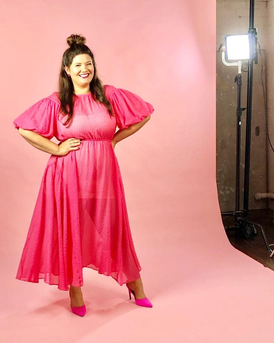 Tanya Hennessy wearing a pink dress and high heels posing for a photoshoot