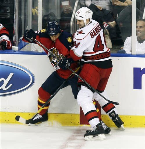 Florida Panthers' Marco Sturm (16) and Carolina Hurricanes' Jay Harrison (44) battle for the puck during the second period of a NHL hockey game in Sunrise, Fla., Saturday, April 7, 2012. (AP Photo/J Pat Carter)