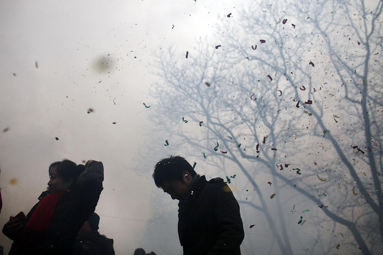 NEW YORK, NY - JANUARY 23: Confetti rains down on people during celebrations in Chinatown for the Chinese New Year on January 23, 2012 in New York City. Celebrations began in New York with the firecracker detonation, intended to ward off evil spirits, to celebrate the arrival of the Chinese New Year, the year of the dragon. Various festivities including singers, dancers and dozens of dance troupes participate in the daylong event which includes marches through the streets of Chinatown. Millions of ethnic Chinese, Vietnamese and Koreans around the world are ringing in the New Year with fireworks, feasting on traditional foods and family reunions.   (Photo by Spencer Platt/Getty Images)