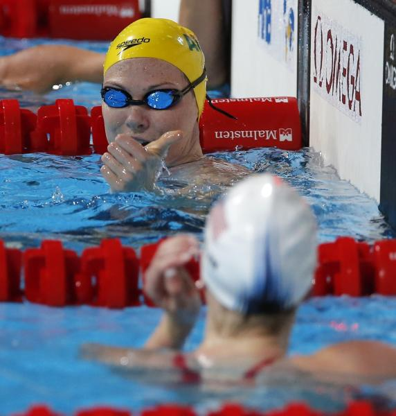 Australia's Cate Campbell, top, gestures to Missy Franklin of the United States after finishing a Women's 100m freestyle heat at the FINA Swimming World Championships in Barcelona, Spain, Thursday, Aug. 1, 2013. (AP Photo/Daniel Ochoa de Olza)