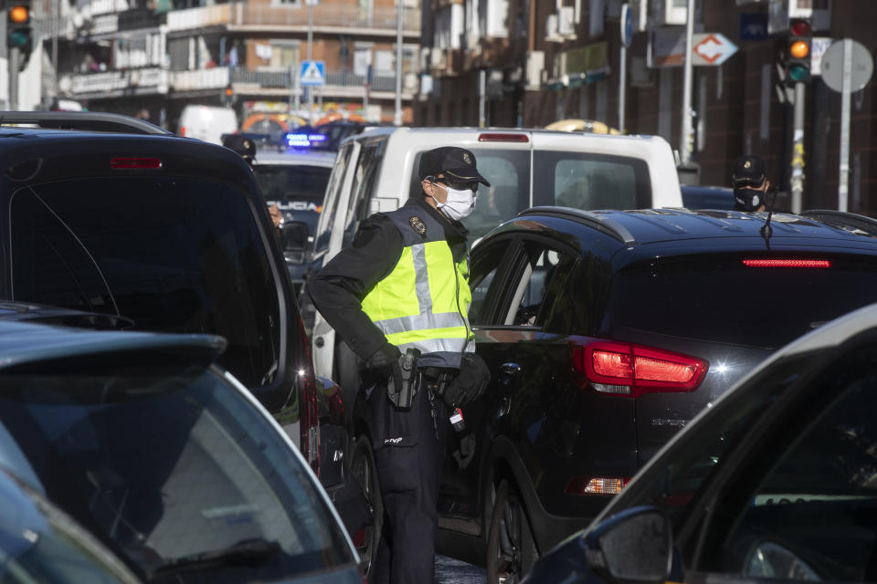 Police mount a checkpoint on the outskirts of Madrid, Spain, Saturday, Oct. 3, 2020. Madrid is on a partial lockdown complying with an order from the Spanish government due to the high COVID-19 cases but determined to fight it in the courts. Measures that ban all nonessential trips in and out of the capital and nine of its suburbs, covering around 4.8 million people. (AP Photo/Paul White)