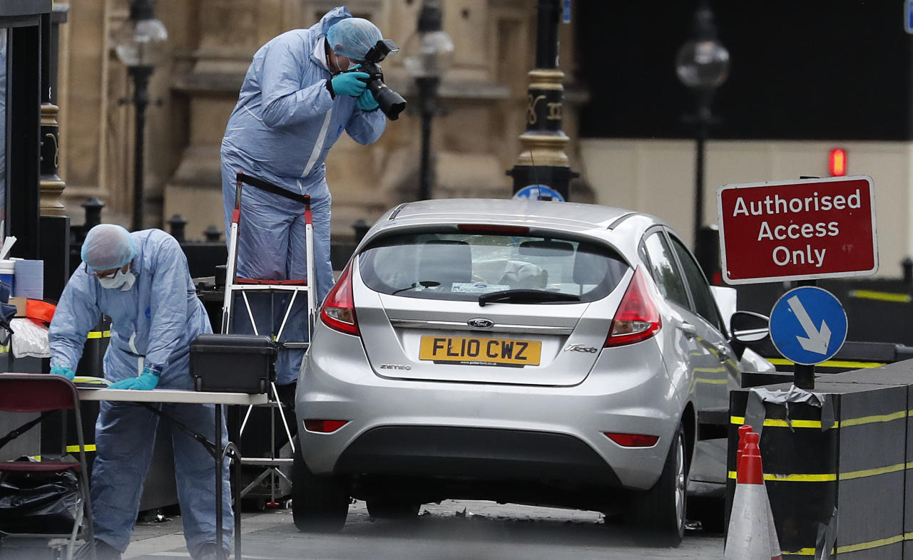 <p>Forensics officers work near the car that crashed into security barriers outside the Houses of Parliament in London, Tuesday, Aug. 14, 2018. (Photo: Frank Augstein/AP) </p>