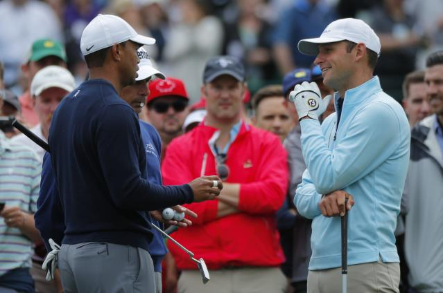 U.S. golfers Tiger Woods (L) and Fred Couples (obscured) talk with competitor and firefighter Matt Parziale (R) on the third tee during the final day of practice for the 2018 Masters golf tournament at Augusta National Golf Club in Augusta, Georgia, U.S. April 4, 2018. REUTERS/Brian Snyder