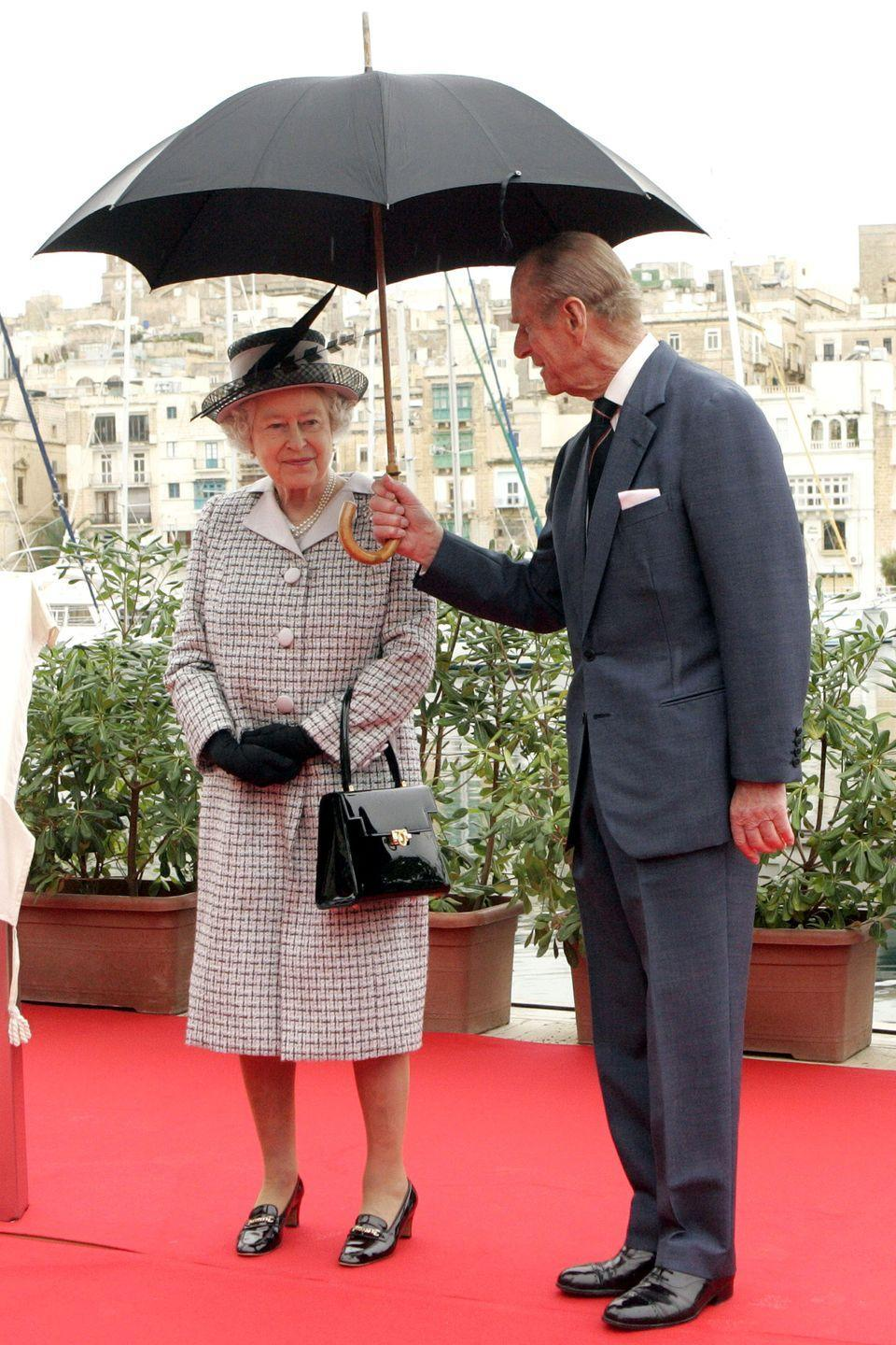 <p>Prince Philip holds an umbrella for Queen Elizabeth at the official opening of The Grand Harbour Marina in Malta. </p>