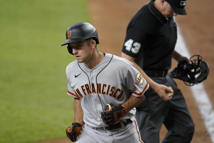 San Francisco Giants' Jason Vosler returns to the dugout after crossing the plate on his solo home run as umpire Shane Livensparger looks on in the fifth inning of the team's baseball game against the Texas Rangers in Arlington, Texas, Wednesday, June 9, 2021. (AP Photo/Tony Gutierrez)