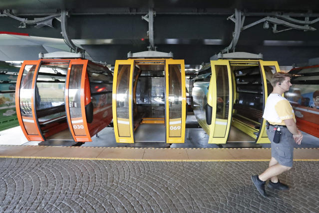 A Disney cast member walks by gondolas as they move from a station to various locations at Walt Disney World on the Disney Skyliner aerial tram, Friday, Sept. 27, 2019, in Lake Buena Vista, Fla. The Disney Skyliner gondolas opening to visitors on Sunday are the latest addition to one of the largest private transportation systems in the U.S. (AP Photo/John Raoux)