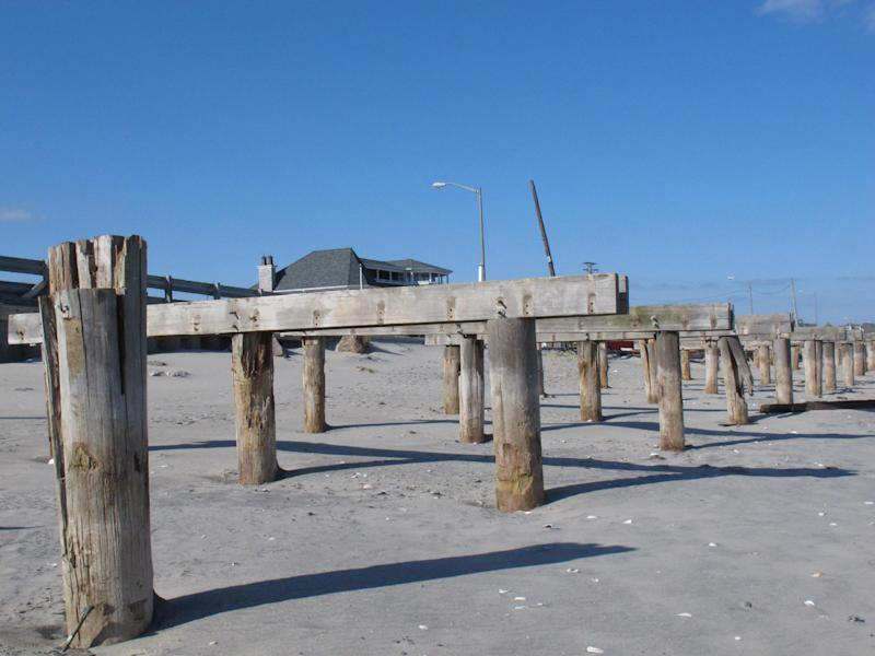 Support pilings for the Avon, N.J. boardwalk, shown here on Feb. 12, 2013, are all that is left of the walkway that was destroyed in Superstorm Sandy.Dogged by legal and environmental woes, Avon is lagging behind some other Jersey shore towns in terms of quickly rebuilding storm-damaged boardwalks. (AP Photo/Wayne Parry)