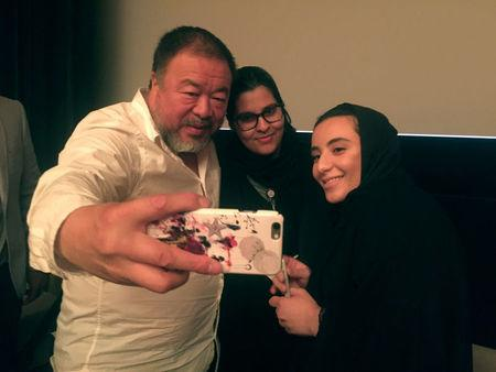 Chinese dissident artist Ai Weiwei takes a selfie with women at the Islamic Art Museum in Doha