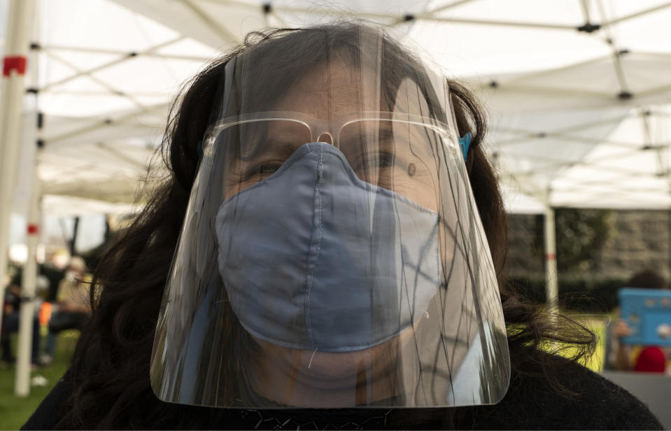 Veronica Lopez, 42, who has Spina bifida, originally from Guatemala, wears a face shield and mask protection, as she waits at the recovery tent for 15 minutes after being vaccinated at the St. John's Well Child and Family Center's COVID-19 vaccination site at the East Los Angeles Civic Center in Los Angeles, Thursday, March 4, 2021. California will begin setting aside 40% of all vaccine doses for the state's most vulnerable neighborhoods in an effort to inoculate people most at risk from the coronavirus more quickly. (AP Photo/Damian Dovarganes)
