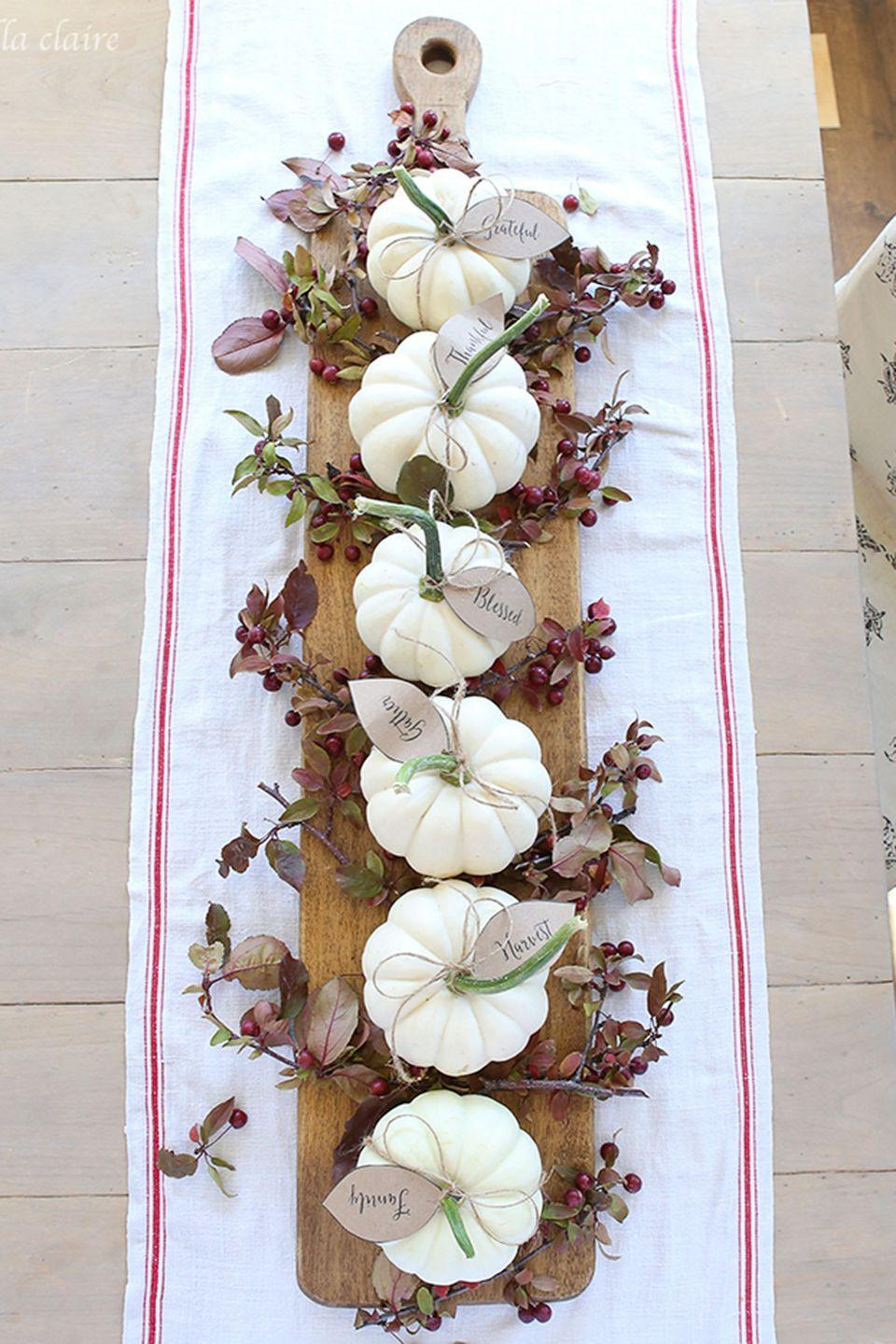 """<p>Tie leaf-shaped tags around your pumpkins and add sprigs of fall picks to create this simply gorgeous centerpiece.</p><p><strong>Get the tutorial at <a href=""""http://www.ellaclaireinspired.com/fall-2015-home-tour/"""" rel=""""nofollow noopener"""" target=""""_blank"""" data-ylk=""""slk:Ella Claire"""" class=""""link rapid-noclick-resp"""">Ella Claire</a>.</strong></p><p><strong><a class=""""link rapid-noclick-resp"""" href=""""https://go.redirectingat.com?id=74968X1596630&url=https%3A%2F%2Fwww.worldmarket.com%2Fproduct%2Flarge-raw-edge-wood-paddle-cutting-board.do&sref=https%3A%2F%2Fwww.countryliving.com%2Fentertaining%2Fg2130%2Fthanksgiving-centerpieces%2F"""" rel=""""nofollow noopener"""" target=""""_blank"""" data-ylk=""""slk:SHOP PADDLE CUTTING BOARD"""">SHOP PADDLE CUTTING BOARD</a></strong></p>"""