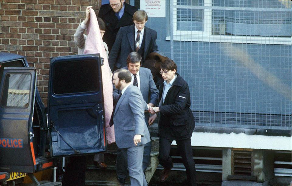 Scottish serial killer, Dennis Nilsen (right), is escorted from Highgate police station to a police van on his way to a court appearance in London, shortly after his arrest in February 1983. Nilsen murdered between 12 and 15 young men between 1978 and 1983. (Photo by Bryn Colton/Getty Images)
