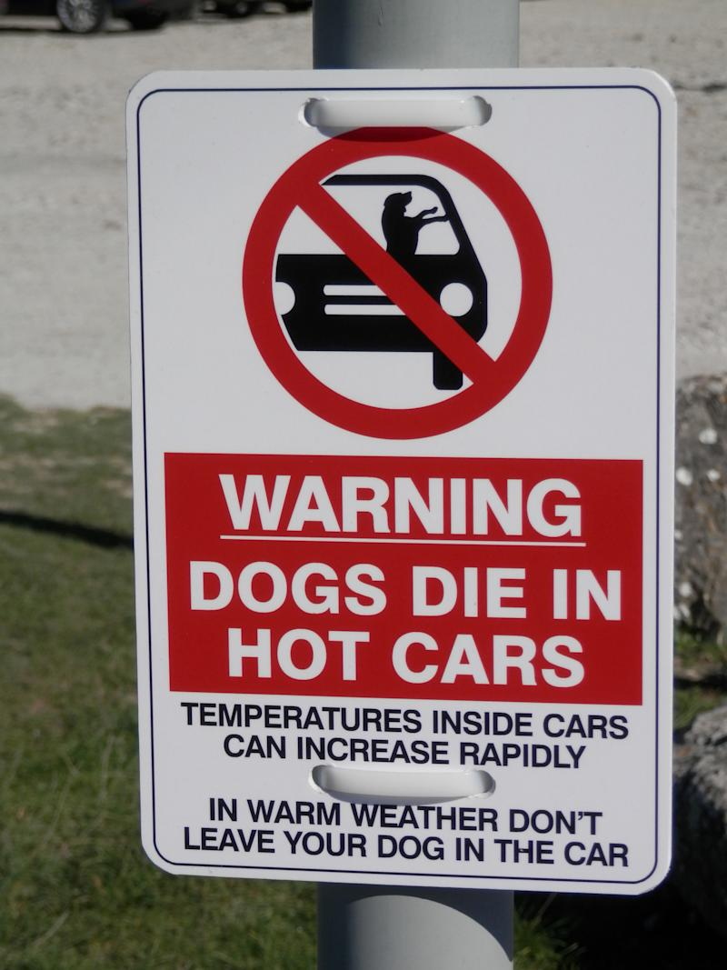 Sign in car park warning against leaving dogs in car in the sun