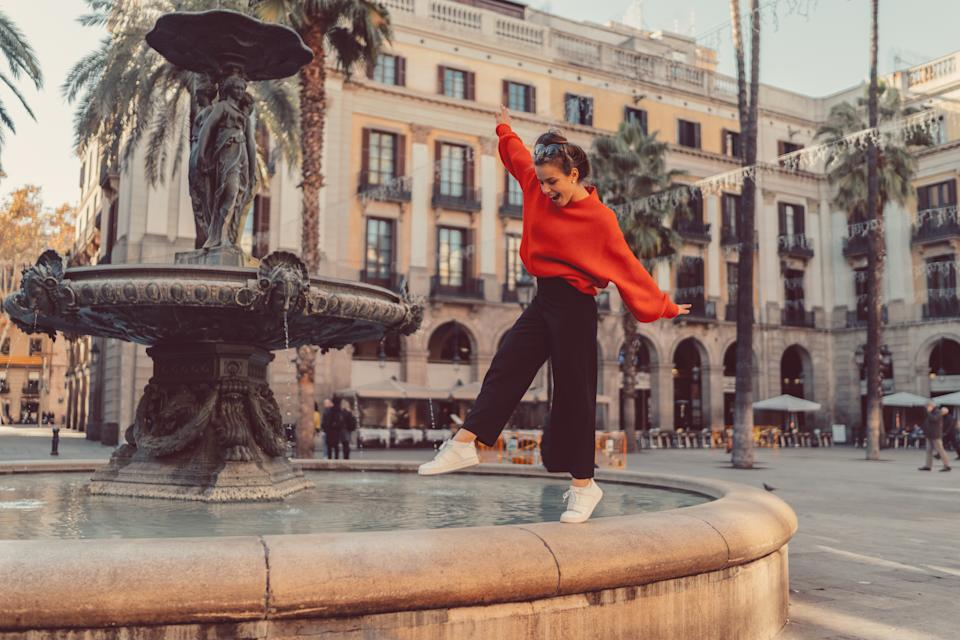 Smiling woman trying to keep balance while walking on one leg at the fountain