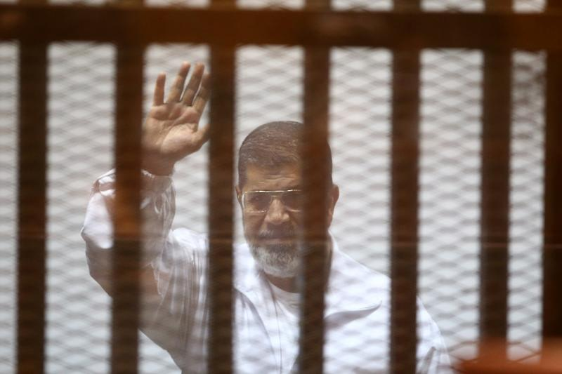 Egypt's deposed Islamist president Mohamed Morsi waves inside the defendant's cage during a trial at the police academy in Cairo on December 7, 2014 (AFP Photo/Ahmed Ramadan)